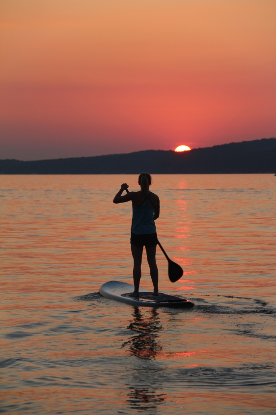 My sister, Abbey, paddle boarding into the sunset